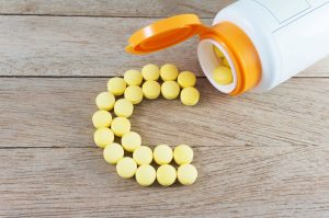 Yellow pills forming shape to C alphabet on wood background