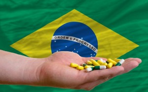 holding pills in hand in front of brazil national flag