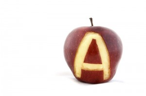 An apple with the letter A carved out of the skin