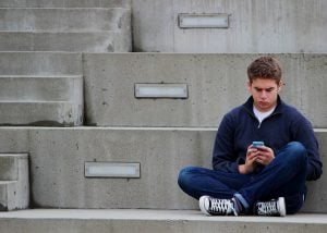 lonely teenager texting mobile phone_oncology news australia