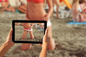 Woman taking pictures on a tablet Girls on a beach