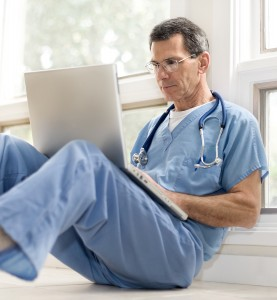senior male doctor with computer