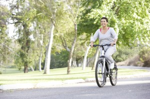 Senior Woman Cycling In Park